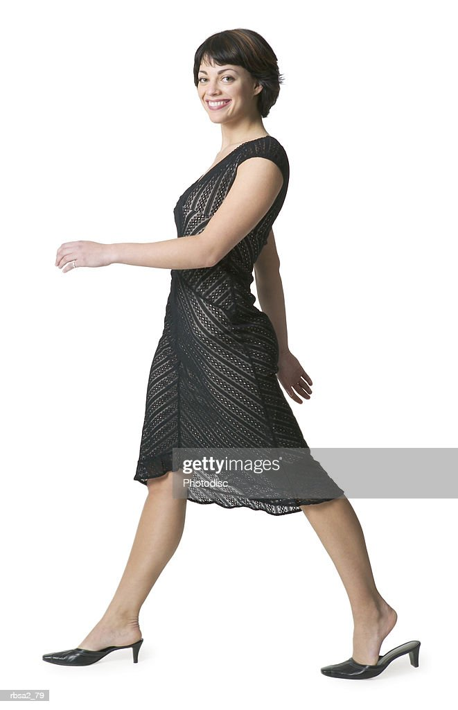 a young attractive caucasian woman in a black dress strolls along and smiles : Foto de stock