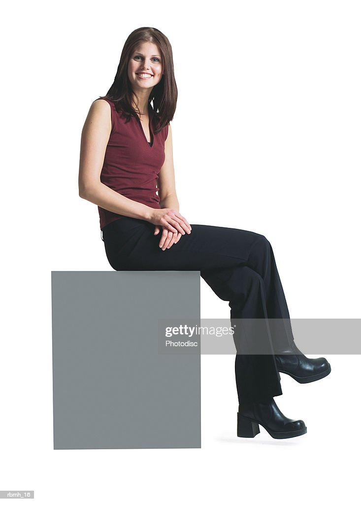 a young attractive caucasian woman in black pants and a red shirt sits atop a blank sign smiling : Stockfoto