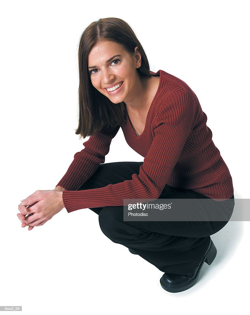 a young attractive caucasian woman in black pants and a red sweater crouches down and smiles : Foto de stock