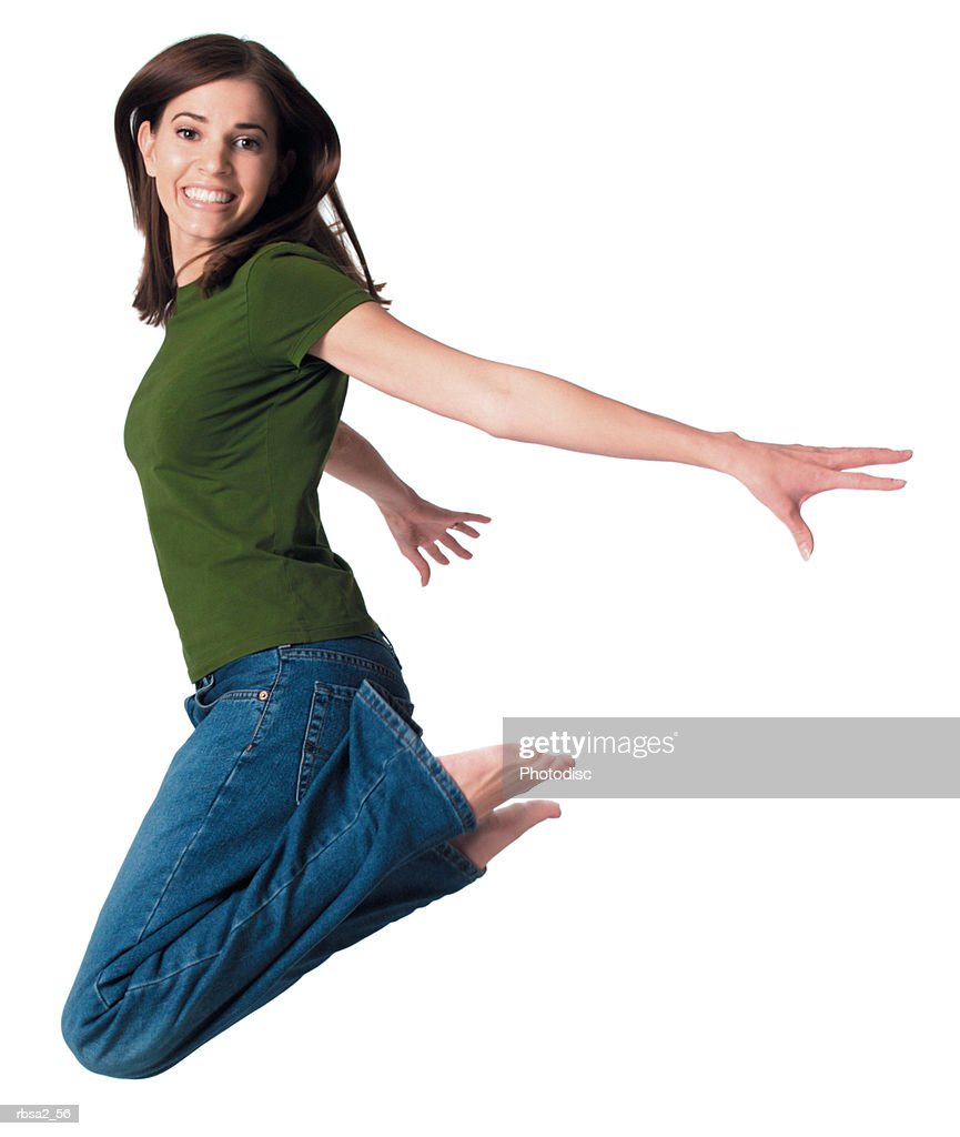 a young attractive caucasian woman in blue jeans and a green shirt jumps up playfully through the air : Foto de stock