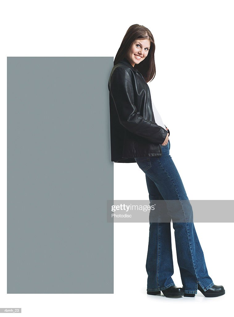 a young attractive caucasian woman in jeans and a leather jacket smiles as she leans her back against a blank sign : Stockfoto