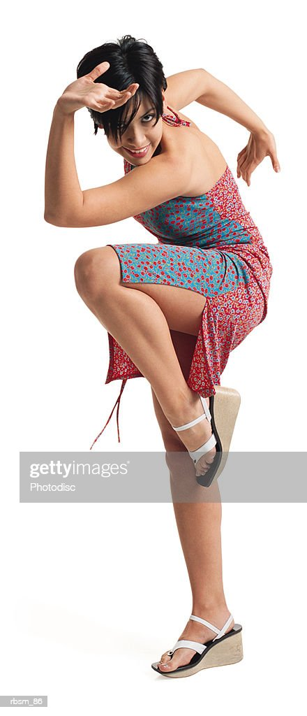 a young attractive latin female dancer in a red and blue sun dress balances on one leg and smiles from behind her arm : Foto de stock