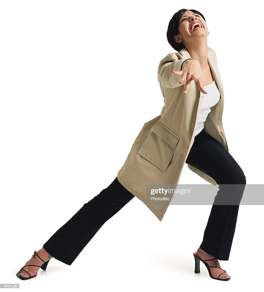 a young attractive latin female in black pants and a tan jacket stretches out her leg and throws one arm forward as she smiles : Foto de stock