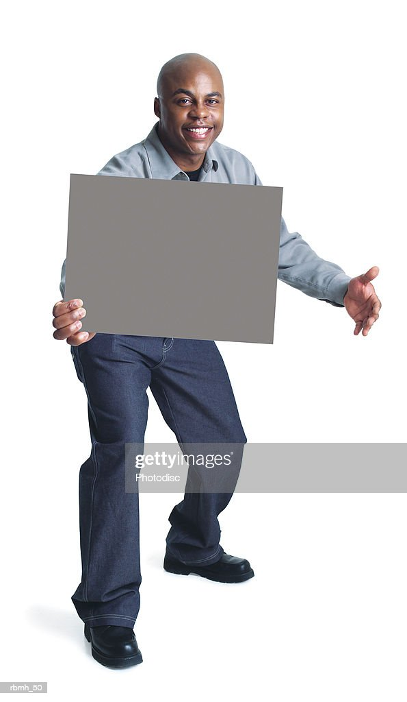 a young bald african american man wearing dark slacks and a grey shirt steps forward with one hand holding a blank sign and one hand out to the side while smiling : Stockfoto