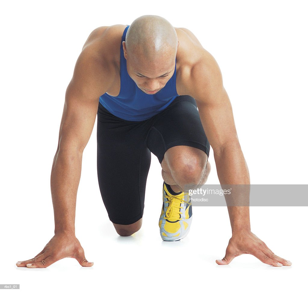 a young bald black male runner wears a blue tank top and leans forward in the starting position : Stockfoto