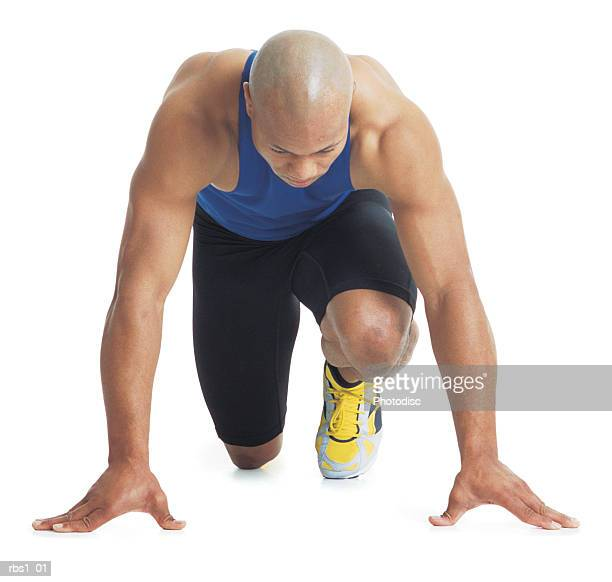 a young bald black male runner wears a blue tank top and leans forward in the starting position - calm before the storm stock pictures, royalty-free photos & images