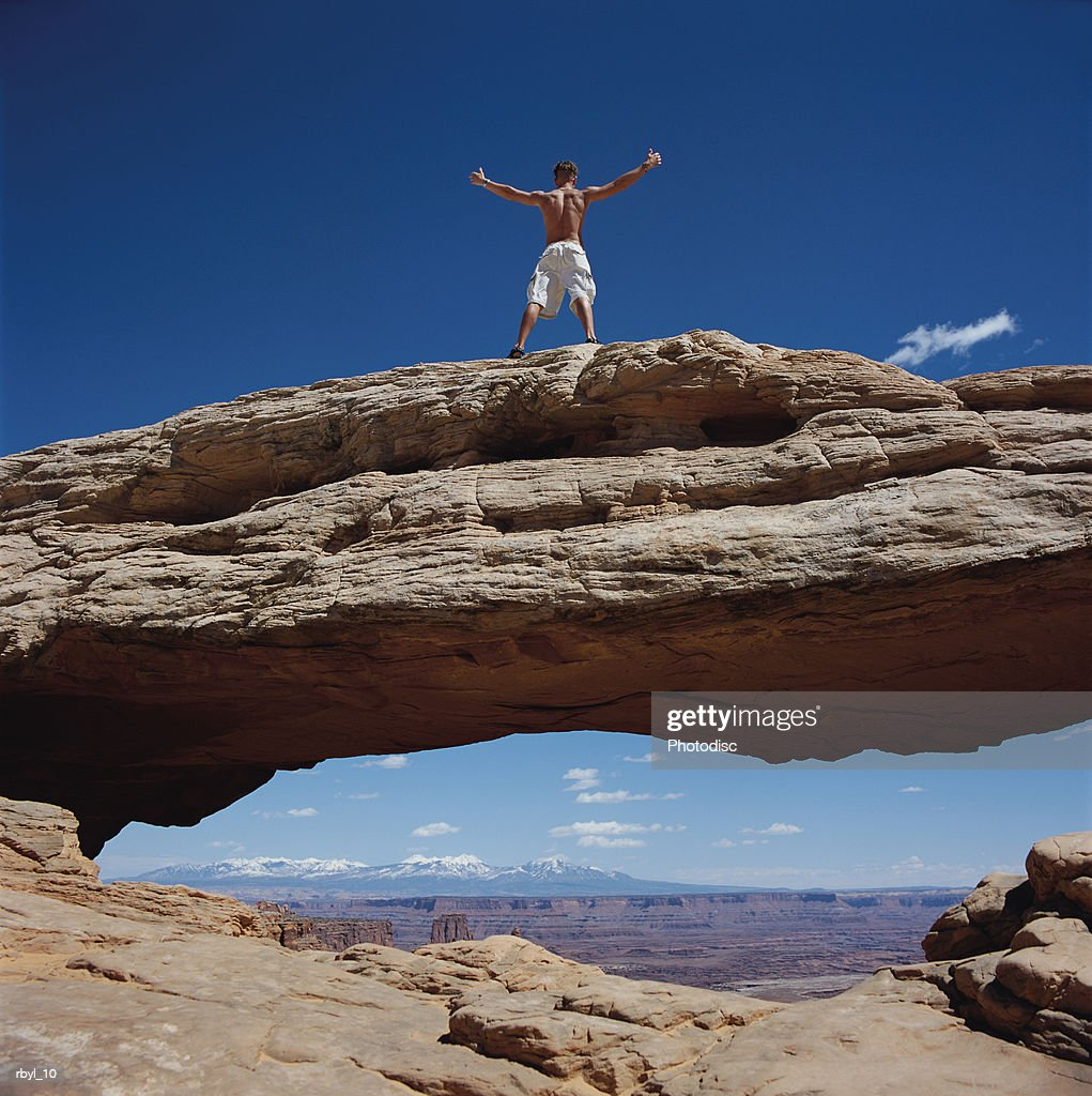 a young bare chested man stands triumphantly on the top of a natural arch in the south utah desert : Foto de stock