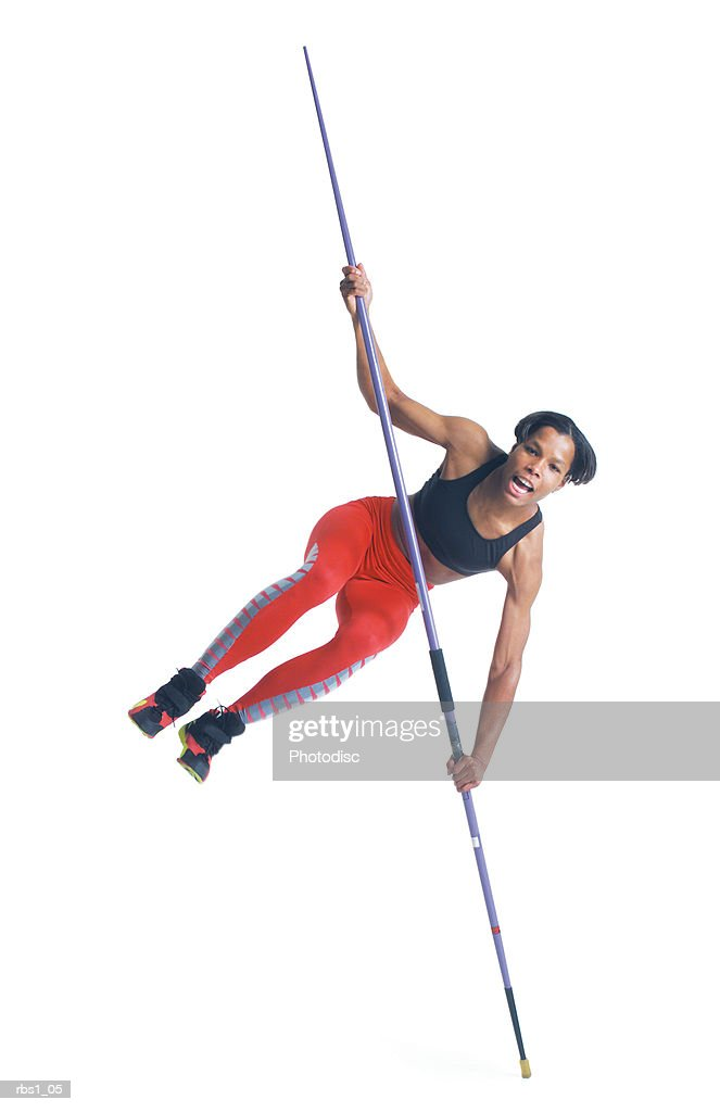 a young black athletic woman in red running pants balances on the tip of her javelin : Foto de stock