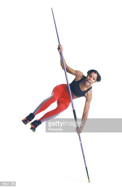 a young black athletic woman in red running pants balances on the tip of her javelin
