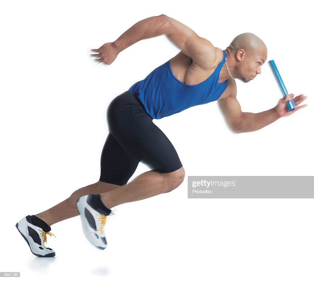 a young black male athlete is bald and wearing a blue tank top while carrying a baton as he begins running : Foto de stock