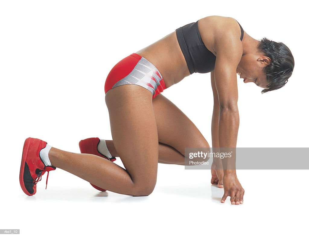 a young black woman in a red and black track uniform crouches forward in a starting position : Foto de stock