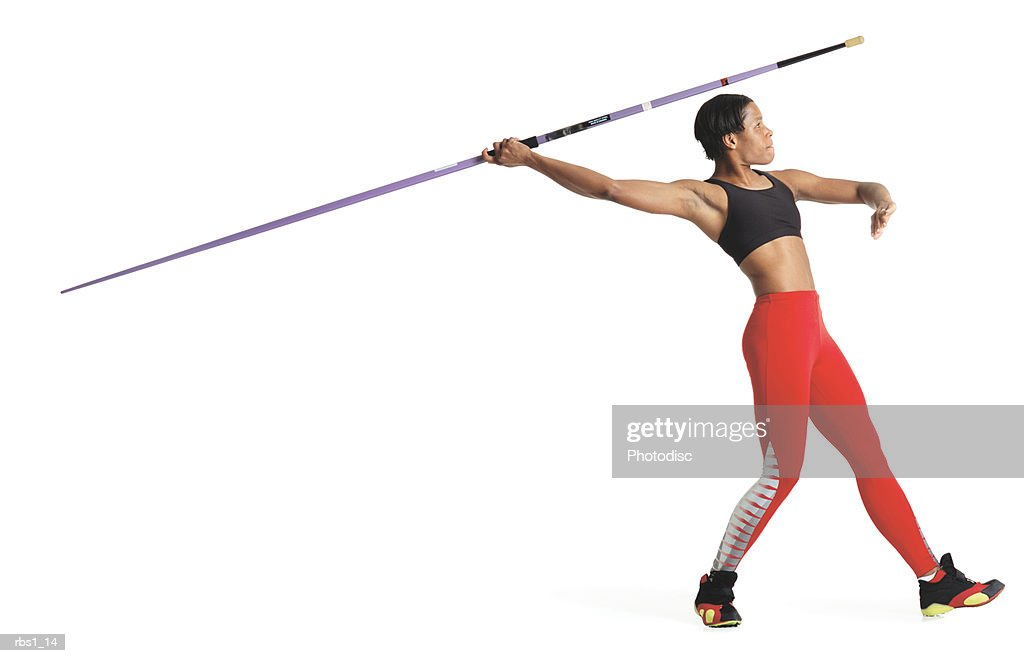 a young black woman is wearing a red track uniform and preparing to throw a javelin : Foto de stock