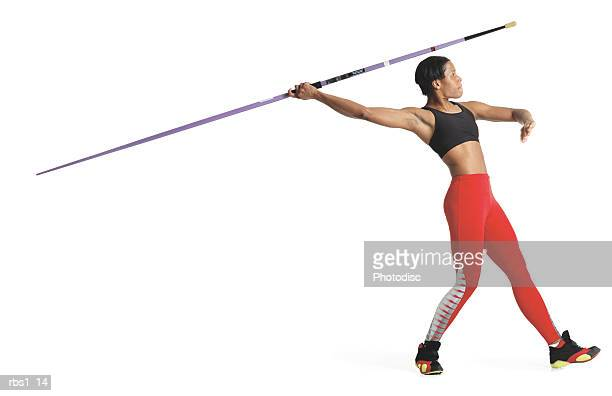 a young black woman is wearing a red track uniform and preparing to throw a javelin - javelin stock pictures, royalty-free photos & images