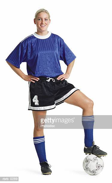 a young blond caucasian female soccer player in a blue jersey and black shorts poses smiling with her foot on the soccer ball - camiseta deportiva fotografías e imágenes de stock