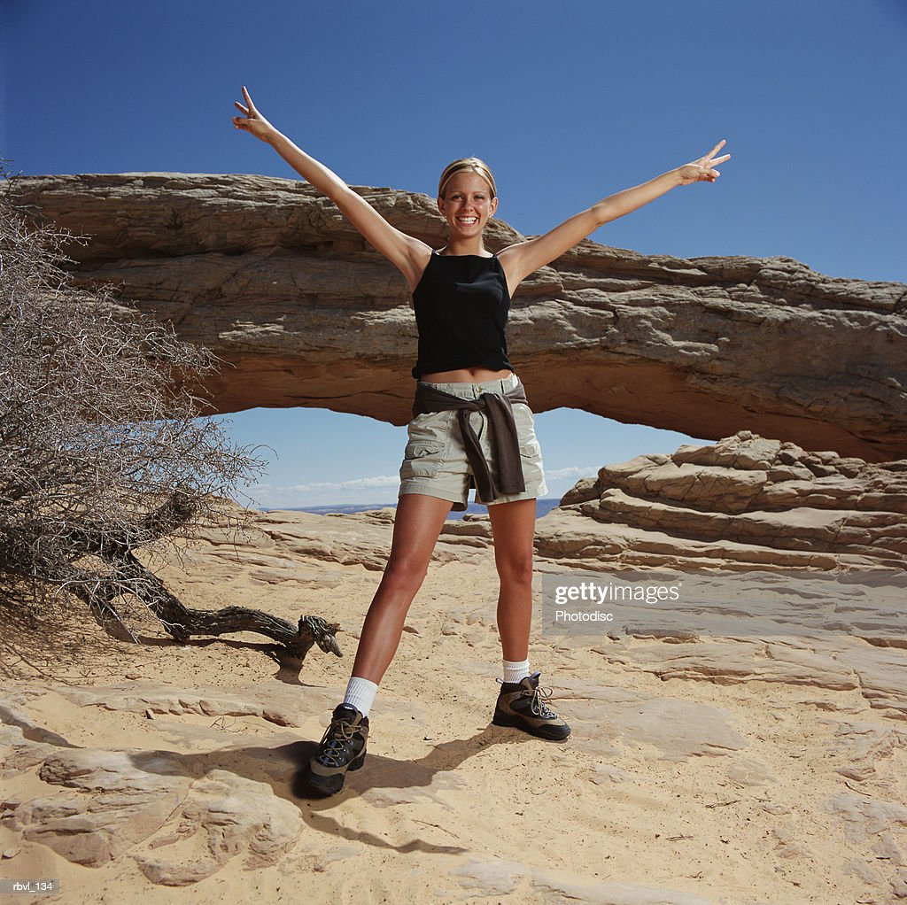 a young blond caucasian woman is wearing shorts and a tank top in front of a natural arch with her arms extended in a peace gesture : Foto de stock