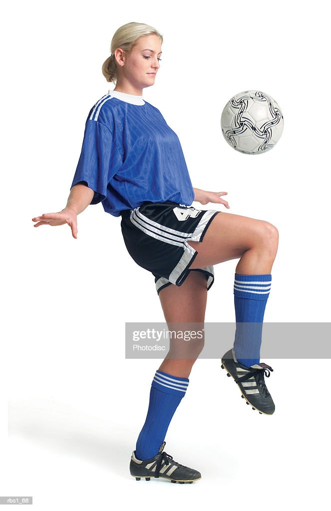 a young blonde caucasian female in a blue soccer jersey bounces a ball on her knee : Foto de stock