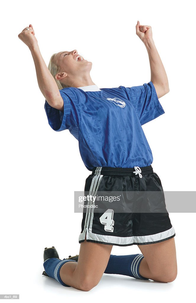 a young blonde caucasian female in a blue soccer jersey kneels on the ground and celebrates a victory : Foto de stock