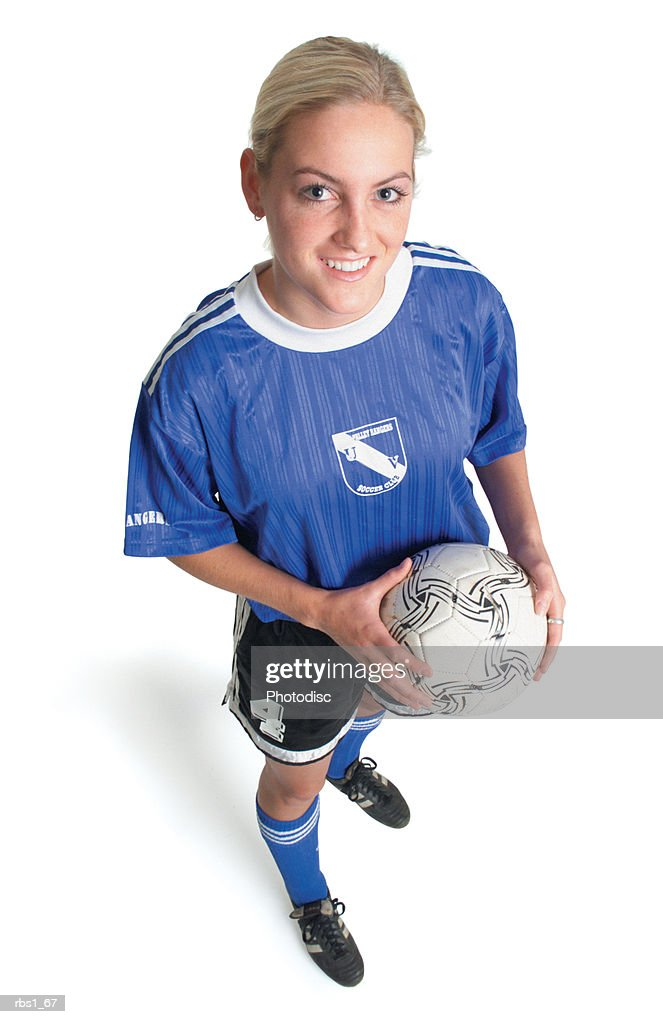 a young blonde caucasian female soccer player in a blue jersey holds a ball and smiles as she looks up into the camera : Foto de stock