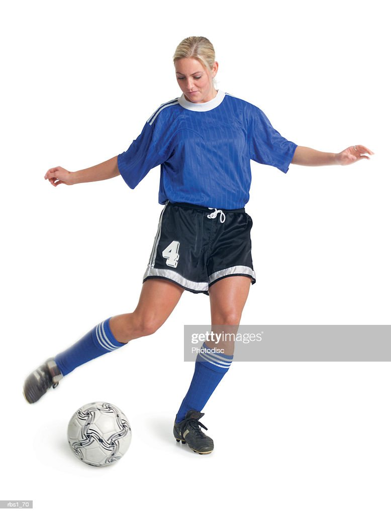 a young blonde caucasian female soccer player in a blue uniform actively kicks a ball away : Foto de stock