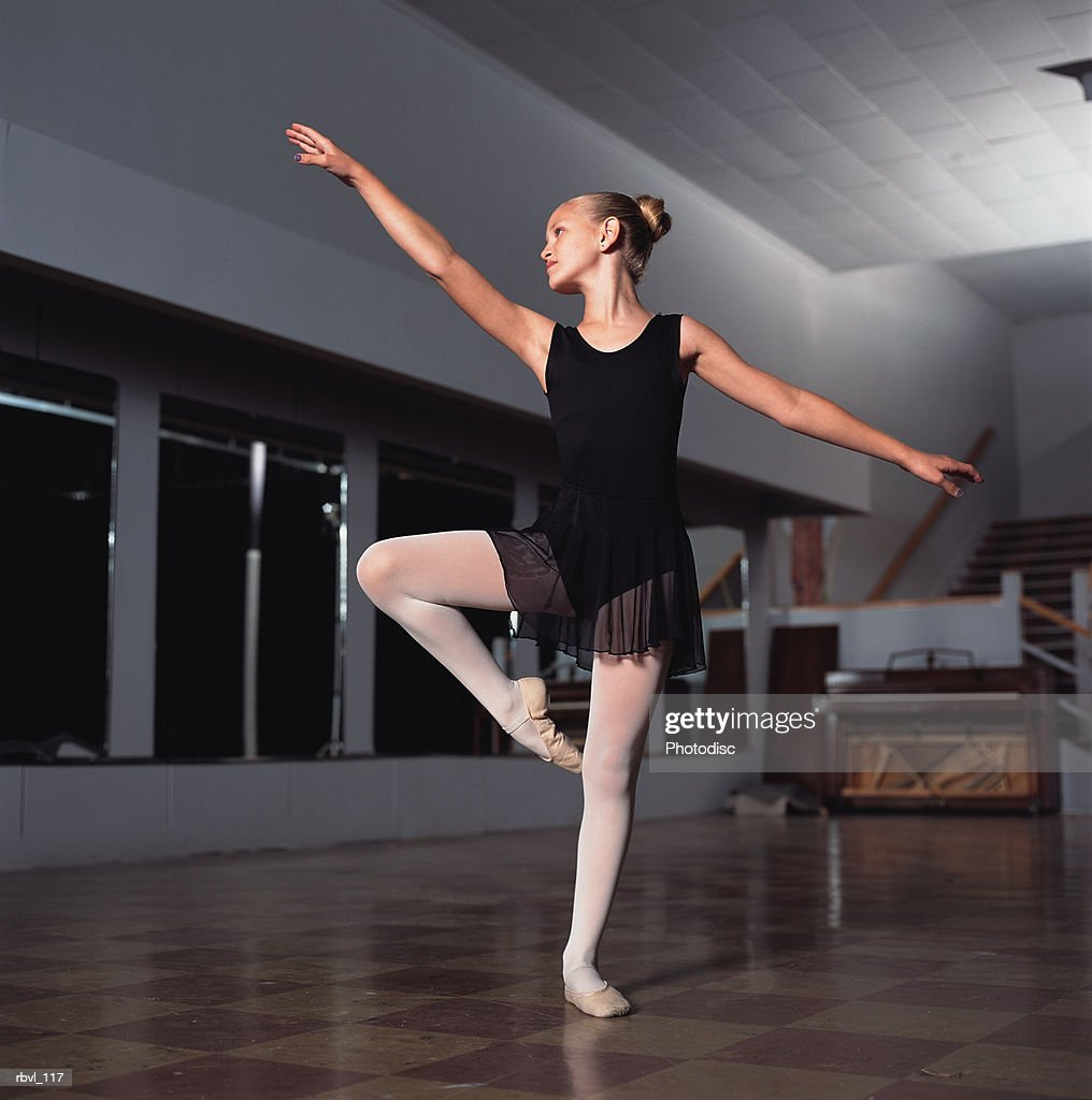 a young blonde caucasian girl in a black skirted loetard is striking a ballet pose inside a studio : Foto de stock