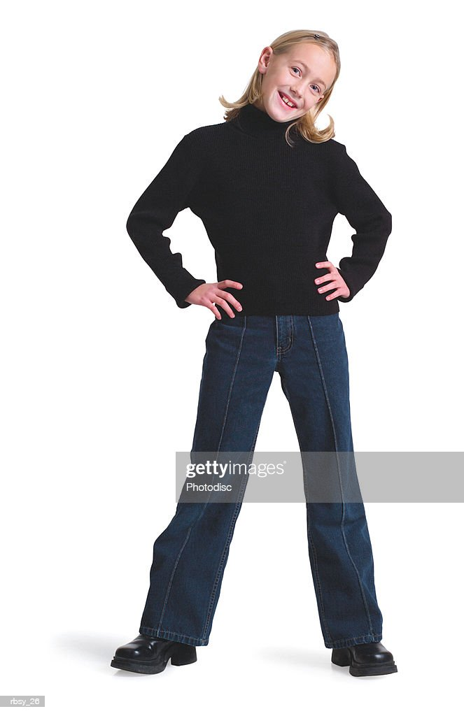 a young blonde caucasian girl in jeans and a black sweater puts her hands on her hips and smiles : Foto de stock