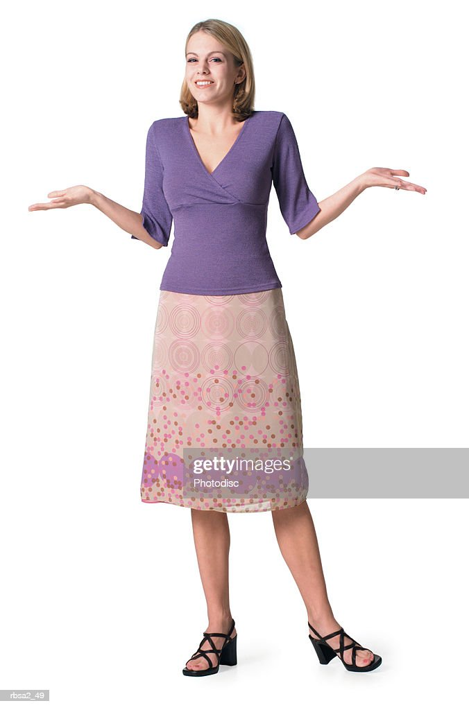 a young blonde caucasian woman in skirt and purple blouse as she shrugs her shoulders and smiles : Stockfoto