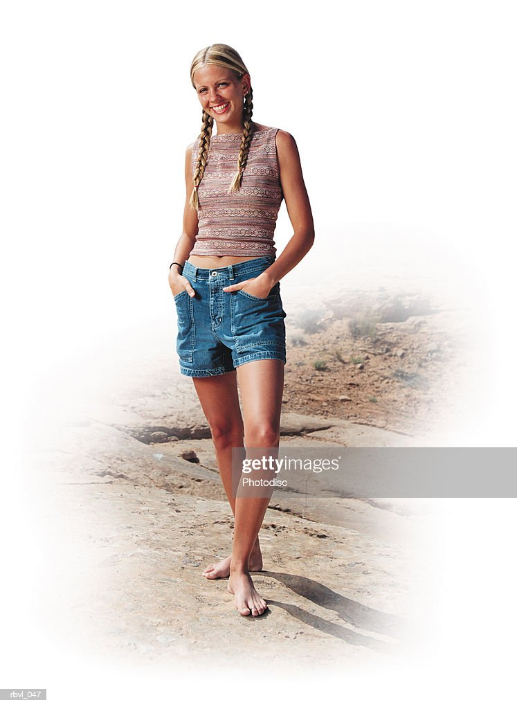 a young blonde caucasian woman in the desert stands with her hands in her shorts pockets wearing a tank top : Foto de stock