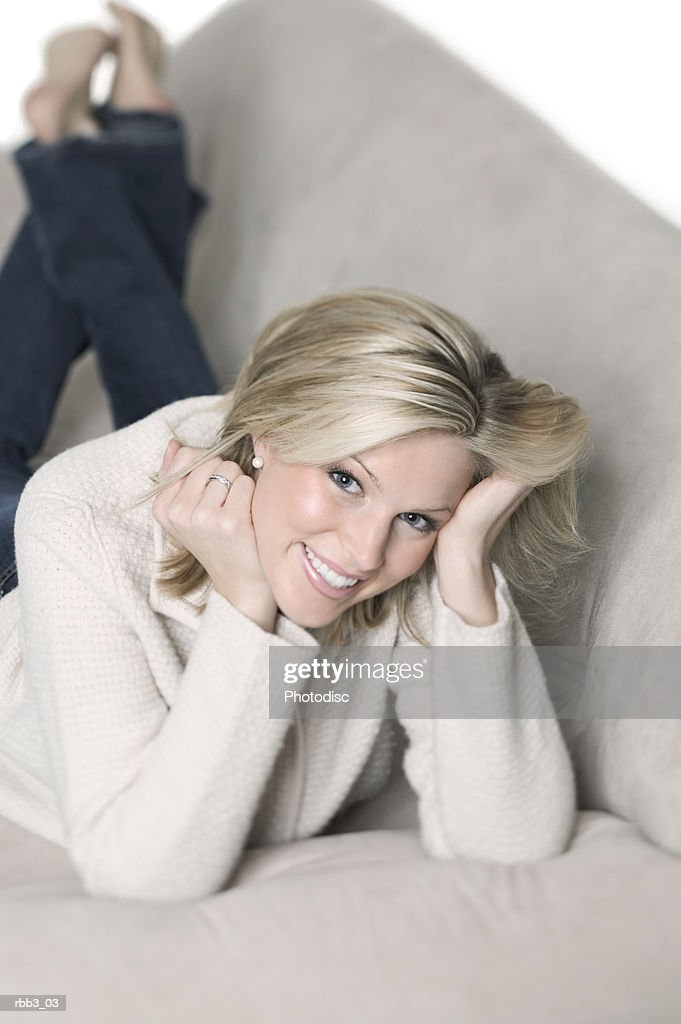 a young blonde caucasian woman lays on a couch and smiles : Stockfoto