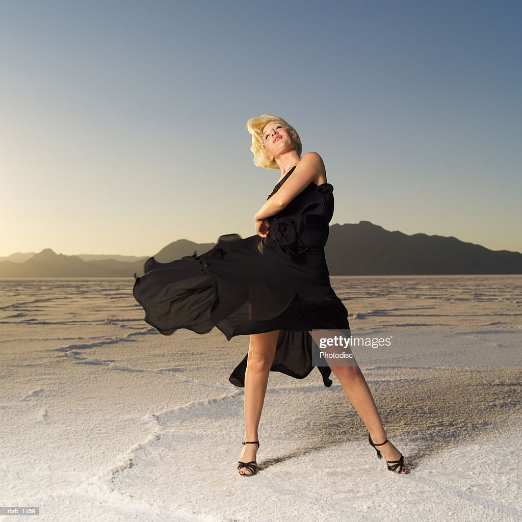 a young blonde woman dressed in a black dress tosses her skirt in a desert setting : Stockfoto