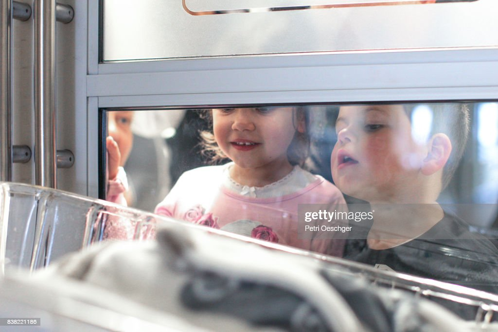 a Young boy and girl meet their new baby brother for the first time. : Stock Photo