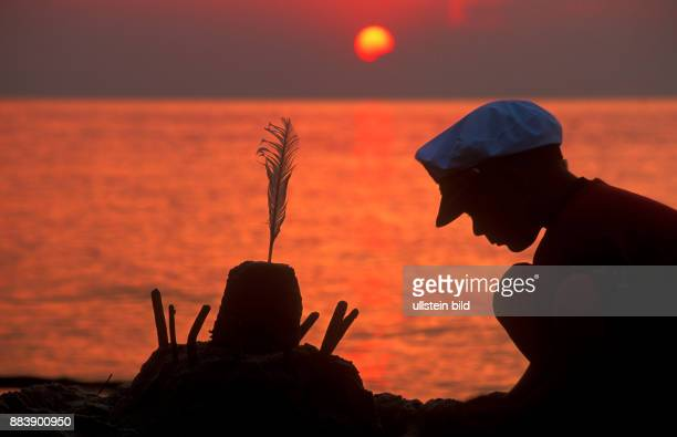 a young boy building a sandcastle at sunset