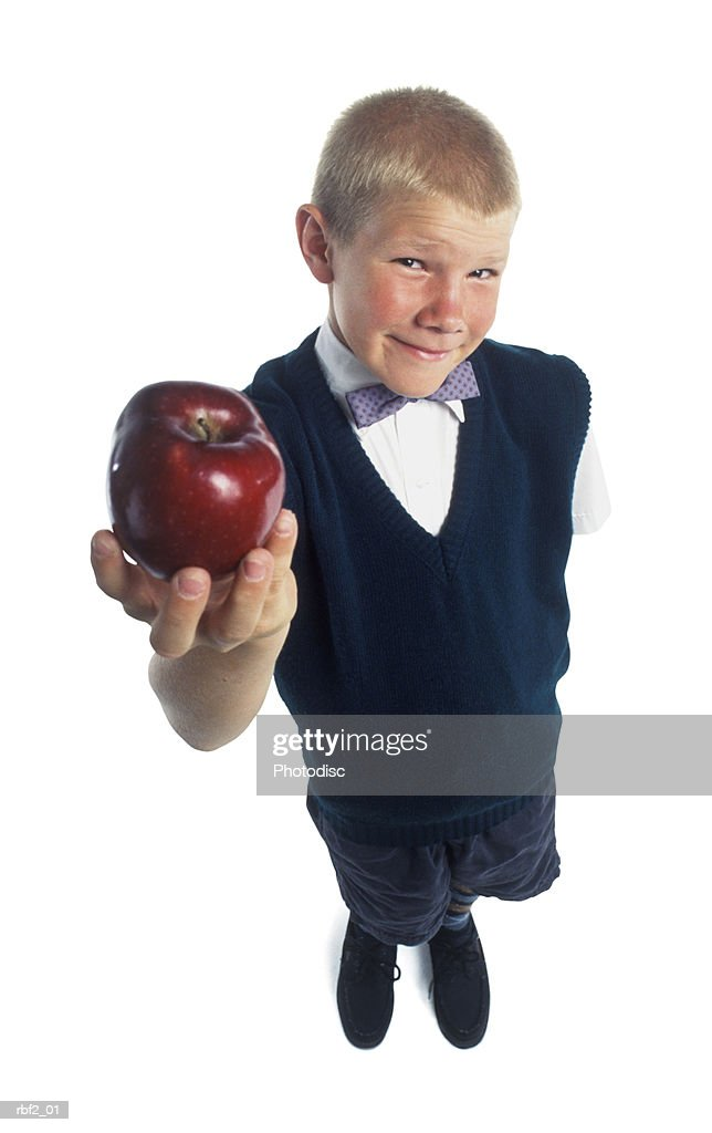 a young boy in a suit holds an apple up to the camera : Stockfoto