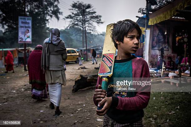 A young boy wandering with his cricket bat in Gangasagar transit camp in kolkata