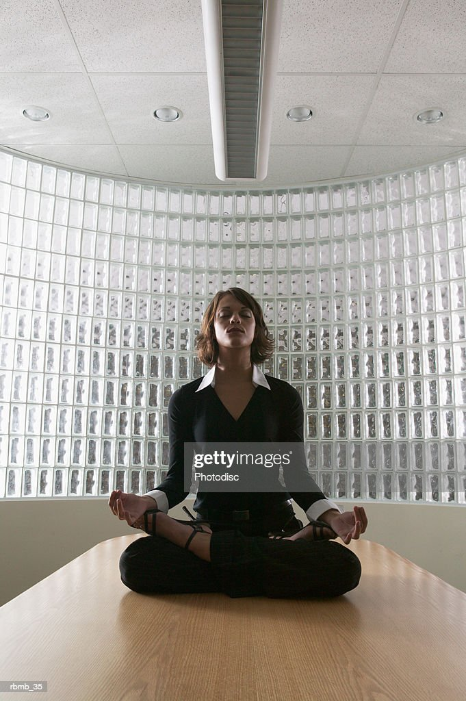 a young brunette business woman in a black outfit sits on a table doing yoga : Stockfoto