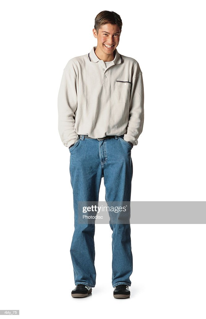 a young brunette caucassian man wearing blue denim jeans with a cream long-sleeve shirt and black shoes has his hands in his pockets as he smiles at the camera : Foto de stock