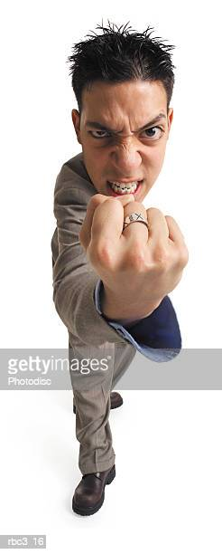 a young business man in a kakhi suit stares angrily at the camera while he shakes his fist at it