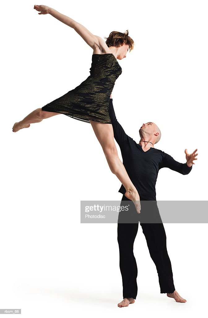 a young caucasian bald male dressed in black lifts up high into the air his caucasian female dance partner who wears a gold and black dress : Foto de stock