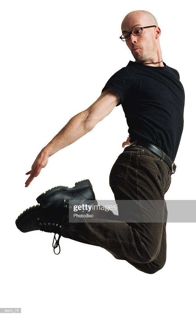 a young caucasian bald male modern dancer dressed in black and wearing glasses jumps up twists his body and reaches for his feet : Stockfoto
