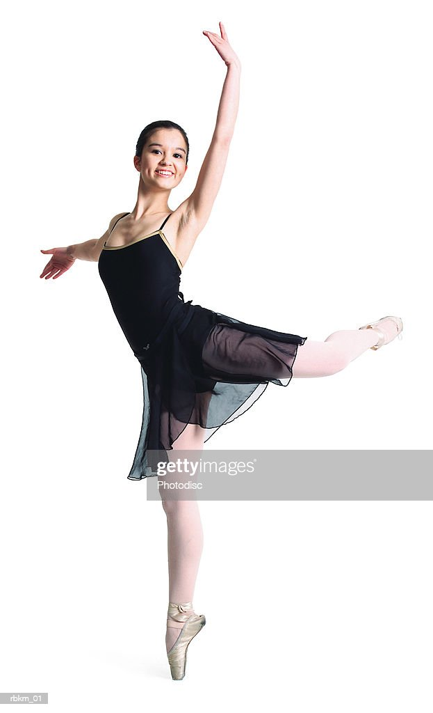 a young caucasian ballet dancer in a black dance outfit balances on her toe and poses : Stockfoto