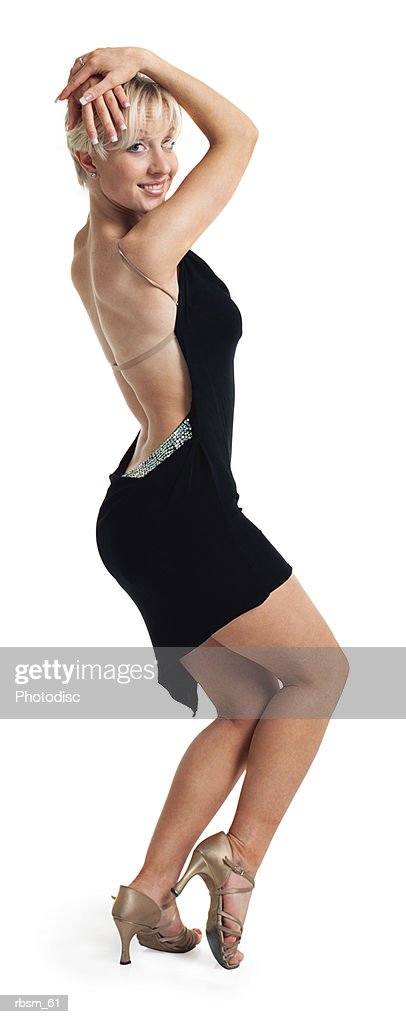 a young caucasian blonde female ballroom dancer in a black backless dress places her hands on her head while turning and smiling : Foto de stock