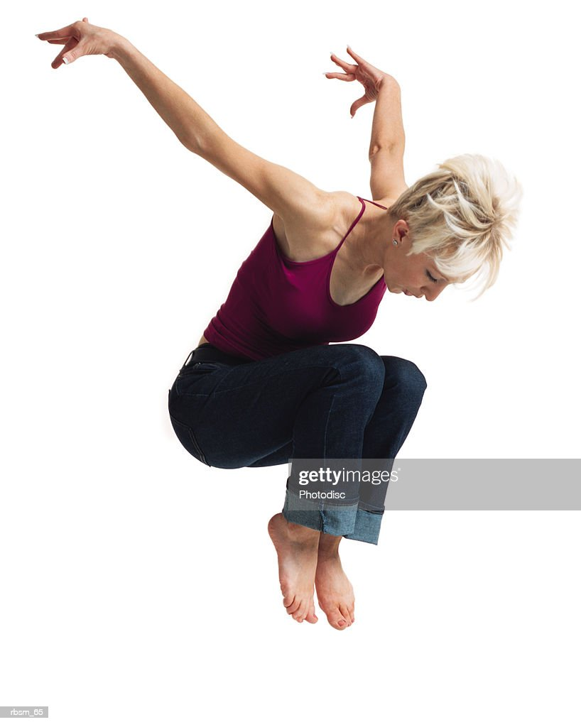 a young caucasian blonde female in jeans and a purple tank top leaps into the air and throws her arms up behind her : Foto de stock