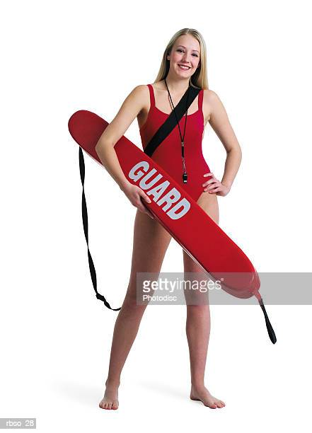 a young caucasian blonde female lifeguard stands posing with her rescue tube - lifeguard stock pictures, royalty-free photos & images