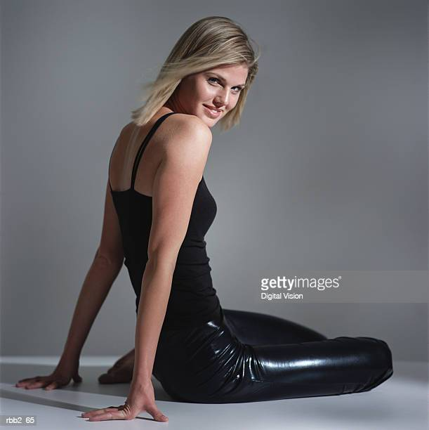 a young caucasian blonde girl dressed in black sits down and smiles flirtatiously into the camera