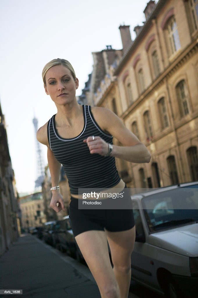 a young caucasian blonde woman in a black running outfit jogs down the streets of paris : Stockfoto