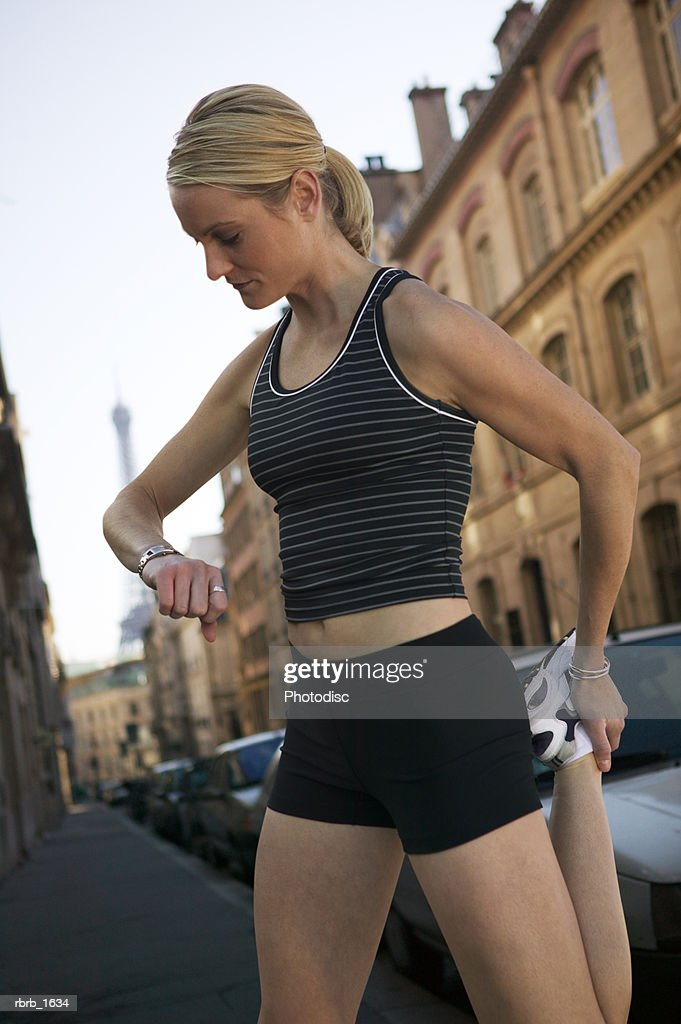 a young caucasian blonde woman in a black running outfit stretches and checks her watch on the streets of paris : Stockfoto