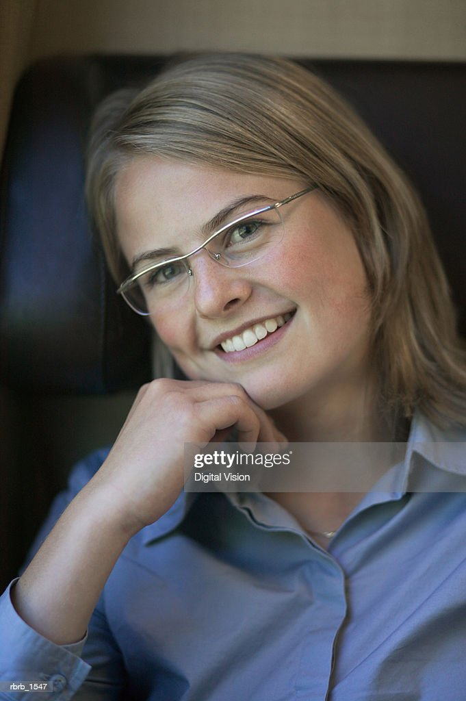 a young caucasian blonde woman in a blue shirt and glasses smiles playfully : Foto stock