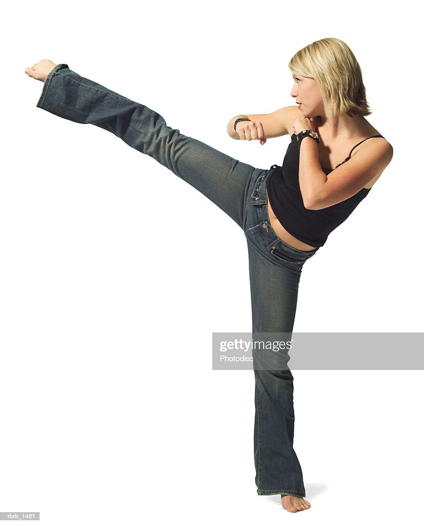 a young caucasian blonde woman in jeans and a black tank top strikes a martial arts pose : Foto de stock