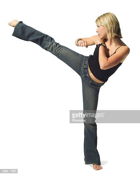 a young caucasian blonde woman in jeans and a black tank top strikes a martial arts pose