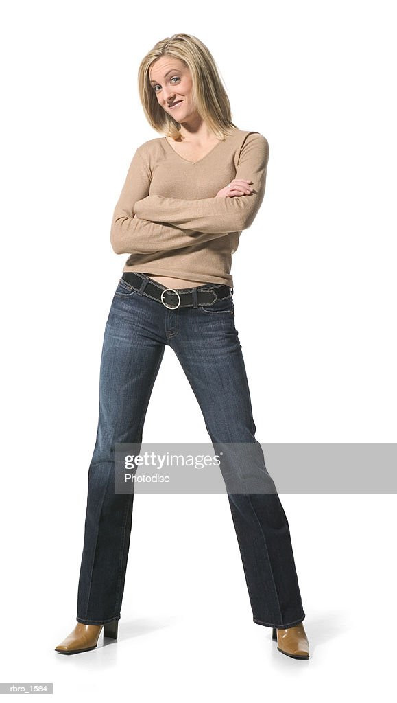 a young caucasian blonde woman in jeans and a tan shirt folds her arms and smilies : Stockfoto