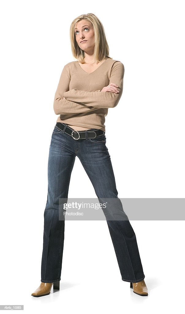 a young caucasian blonde woman in jeans and a tan shirt folds her arms and glances upward : ストックフォト